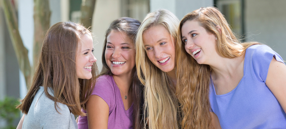 4 female friends smiling