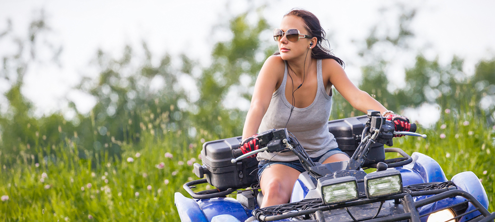 woman riding an all-terrain vehicle in a field